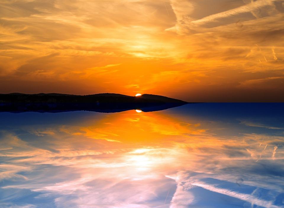 Pemandangan Indah Di Danau Saat Matahari Mengintip Di Balik Gunung